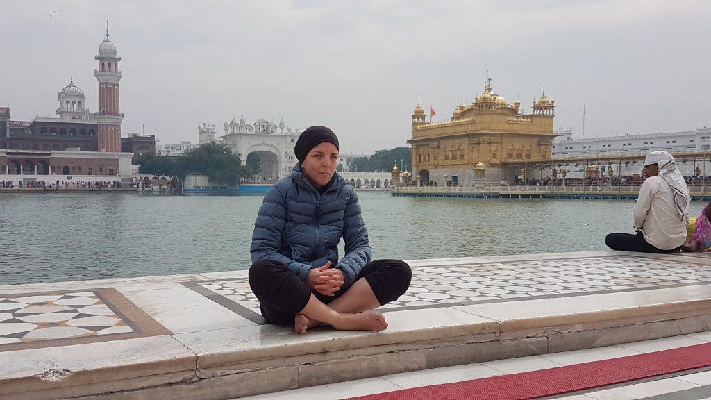 Conchi sentada en el suelo, a orillas del lago que la separa del templo de oro en Amritsar