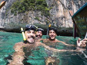 En el mar, tres chicos haciendo buceo